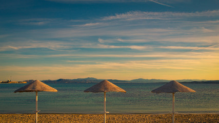 three umbrellas on the beach in the evening sun