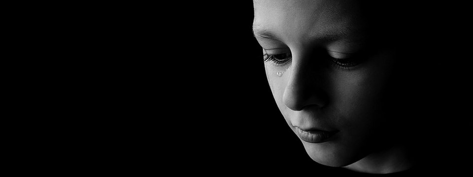 The sad boy with tears in their eyes on a black background