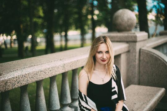 Портрет красивой девушки со светлыми волосами. Девушка сидит вы парке на скамейке