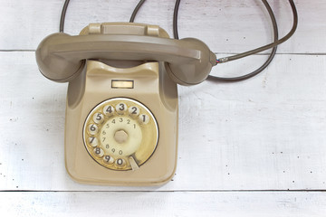 Old telephone on white wooden background