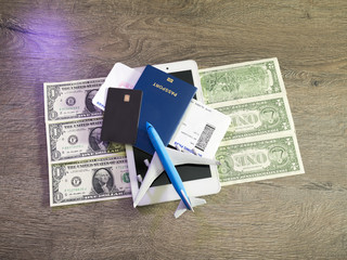 travel concept with tablet, credit cards and flight tickets on dark table