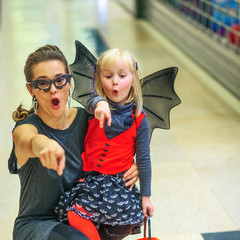 mother and child on Halloween at mall pointing at something