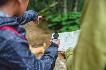 Daughter and mother hiking in forest and using compass