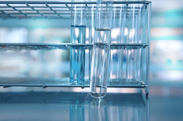 glass test tube with water in metal rack in chemical science laboratory background