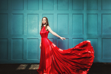 Stylish Woman in Red Dress. Glamourus Beautiful Fashion Model wearing Evening Gown on Blue Background