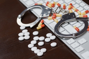 Handcuffs and pills over computer keyboard