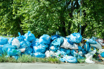 Blue garbage bags full of trash left on the street pollute the city