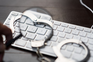Handcuffs on laptop keyboard through a magnifying glass
