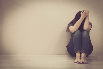 sad woman hug her knee and cry. The depression woman sit on the floor. Teenager girl with depression sitting alone on the floor in the dark room. Toned photo
