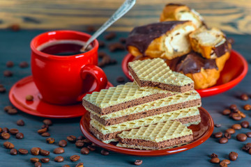 Coffee, waffles and cakes on a wooden background