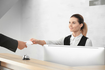 Female receptionist giving key card from hotel room to client