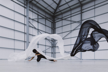 A male dancer performing floorwork with black and white sheets of silk waving around him