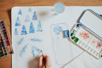 Artist painting watercolor tree branch in her studio