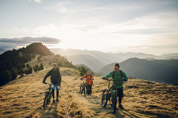 A group of men with his mountain bike going up the mountain at the sunrise