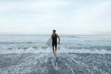 Mature surfer man heading out of the water
