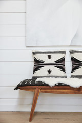 Wood bench with pillows in farmhouse hallway