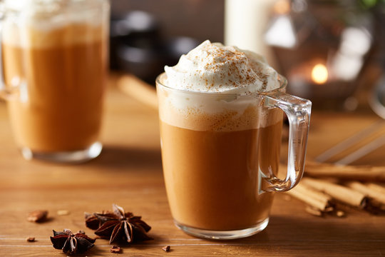Glass cup of pumpkin spice latte with whipped cream.