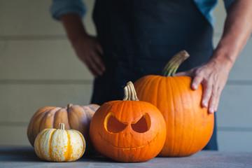 Man standing behind bunch of pumpkins for halloween