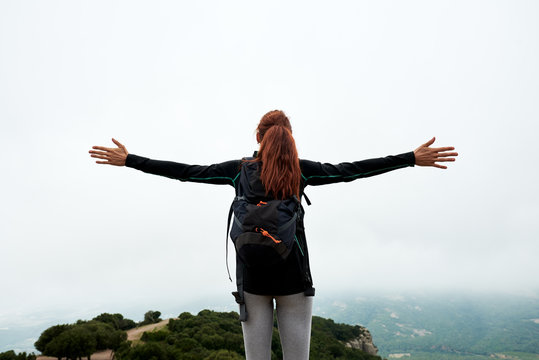 Tourist on mountain with arms wide open