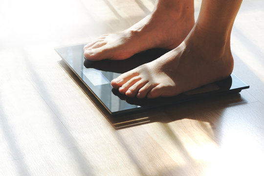 Feet on a scale for weight control after bathroom. Empty copy space for Editor's content.