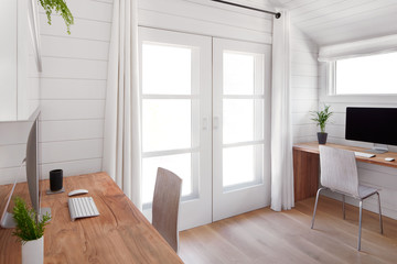 Home office in rustic Farmhouse cottage with white oak wood floors and shiplap walls
