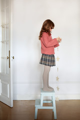 Little girl standing on stool and decorating home for Christmas