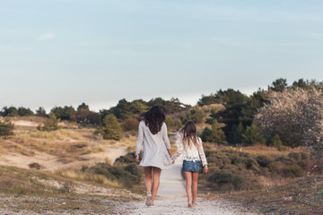 Mother and daughter walking on a path in the dunes