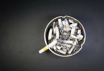 Isolated cigarette ashtray with cigarette kretek burning