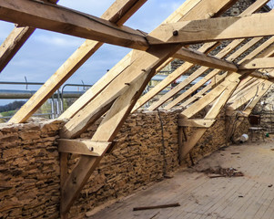 Old typical stone wall house undergoing a roof renovation - French countryside