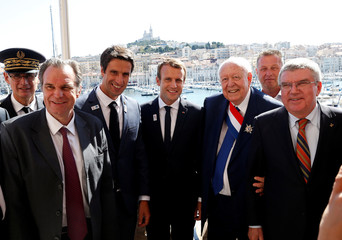 French President Emmanuel Macron poses with President of the International Olympic Committee (IOC) Thomas Bach and officials after a press conference in Marseille