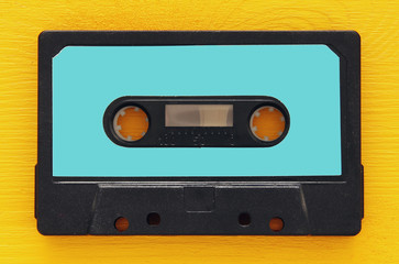 Retro cassette tape over yellow wooden table. top view. copy space