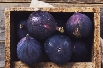 Ripe purple figs in rusted wooden box