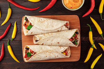 Mexican burritos with cheese salsa, and chili peppers