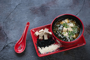 Red tableware with miso soup on a dark textured stone background, studio shot