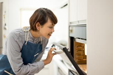 オーブンを開ける若い女性