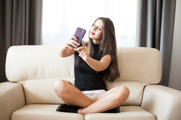 Smiling Beautiful gorgeous young woman taking a selfie in the room. Lifestyle and fun