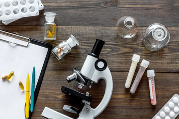 Laboratory test. Microscope, pills, test tube on wooden background top view