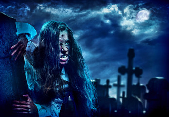 Undead zombie scary girl on halloween graveyard at night on dark clouds sky background. Woman in zombie apocalypse hunting outdoor. Behind monster cemetery with crosses. Moon comes out from clouds
