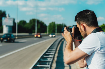 Man photographing cars on the road.