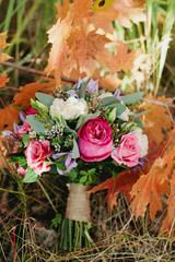 wedding bouquet with colorful flowers on the autumn leaves