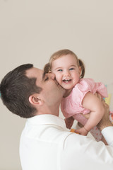 Father lifting up his daugher in the air and kissing her cheek