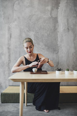 Woman Sitting and Pouring Herself some Tea.