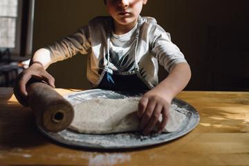 child making pizza
