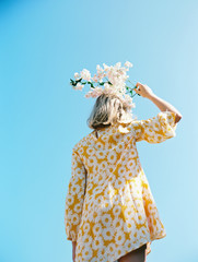 blonde girl with yellow floral dress against blue sky with flowers on her head