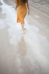 Young happy woman walking on the beach