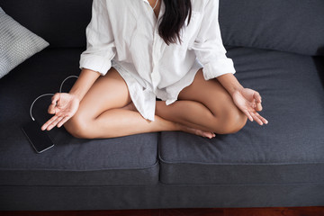 Unrecognizable woman meditating at home