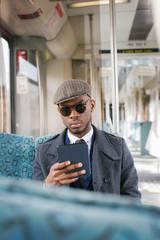 Portrait of Stylish Black Businessman E-Reading in Train
