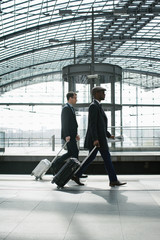 Two Young Business Travelers Walking With Carry On Suitcases in Modern Train Station