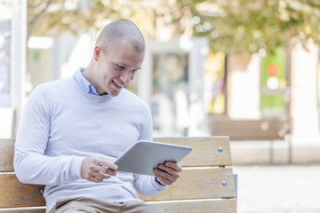 Handsome young smiling  man, student  uses digital tablet