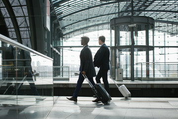 Two Business Travelers Walking With Carry On Suitcases in Modern Train Station